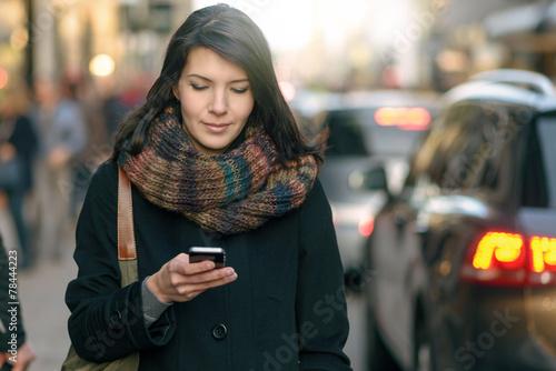 Leinwanddruck Bild Modische junge Frau schreibt mit ihrem Handy eine Nachricht
