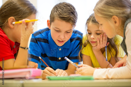 group of students talking and writing at school - 78444226