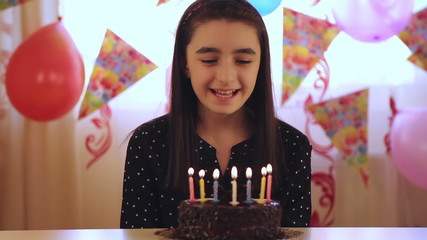 Happy young girl blowing out candles on a birthday cake