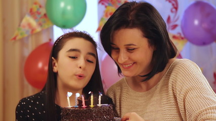 Happy mother and daughter blowing candles of birthday cake