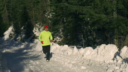 Man running in the forest at winter, steady, slow motion 240fps