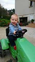 Littla boy first time on tractor toy vehicle want to be a farmer