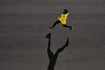 Top view athlete runner training at black road in yellow