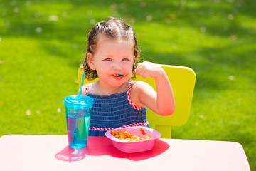 Toddler kid girl eating macaroni tomato pasta