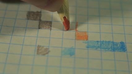 The child's hand draws the orange square