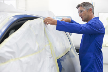 Technician preparing car to be spray painted
