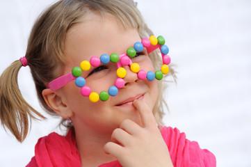 Portrait of cute little girl wearing funny glasses, smarties