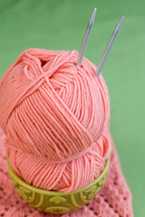 Hank yarn pink skein of yarn and knitting needles