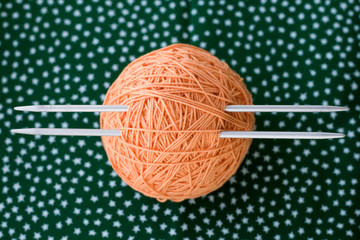 A bright orange ball of yarn and needles for knitting lying