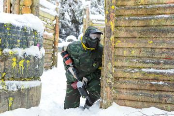 Paintball player with marker sitting on snow near wooden fortifi