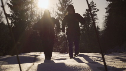 Couple running in the forest on snow, steady, slow motion 240fps