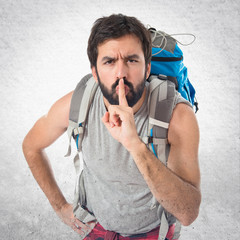 Backpacker making silence gesture over isolated white background