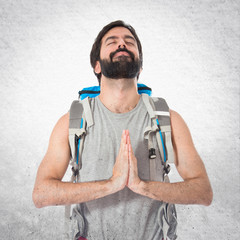 Backpacker in zen position over white background
