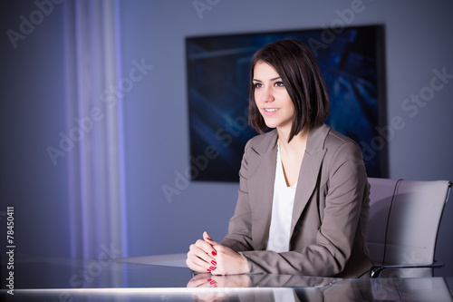 Beautiful television announcer at studio during live broadcast - 78450411