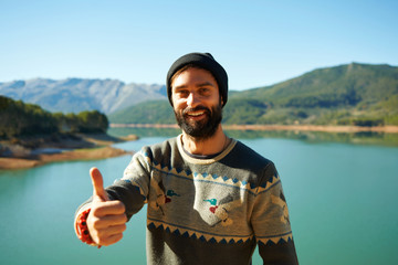 Summer fun man showing thumbs up smiling happy bearded model.