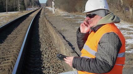 Railway employee  talking on the cell phone near the railway