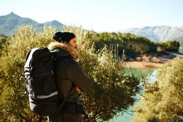 Hiking. Adventure hiking man. Portrait in mountain landscape.