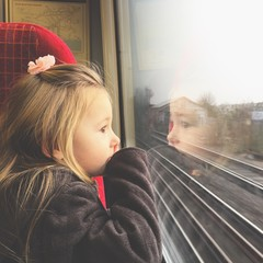 Girl looking through train window