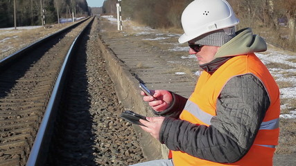 Railway employee  with cell phone and tablet PC near the railway