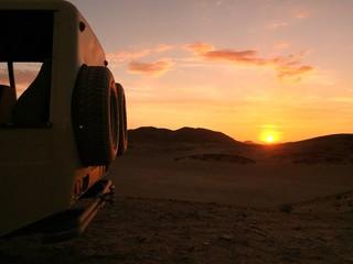 Namibia, Hoanib, 4x4 in desert at sunset