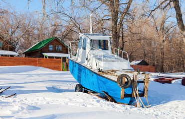 Small ship on the bank of river in winter