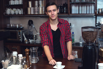 Young barista  at cofeeshop cafe made a cup of coffee and smile