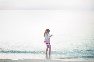 Japan, Okinawa, Girl (12-13) texting while wading in sea