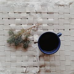 Mug of coffee and pine twig