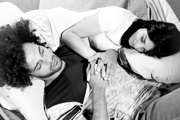 Beautiful happy couple sleeping in bed black and white portrait