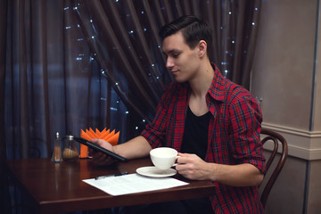 Attractive man hipster uses tablet while drinking tea coffee