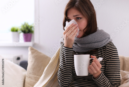 Sick woman covered with blanket holding cup of tea sitting on - 78452674
