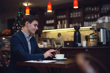 Young attractive businessman in a suit drinking coffee and using