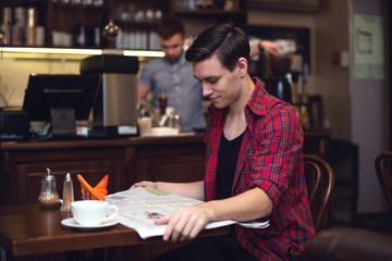Young attractive student drinking coffee and reading newspaper