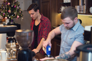Two hipsters working in a coffee shop making orders cleaning the