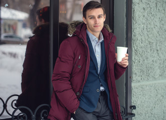 Young man in winter coat woth coffee to go standing against the