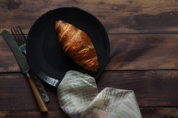 Croissant on plate, napkin and eating utensil on wooden table