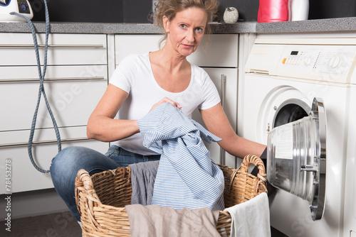canvas print picture Frau lädt Wäsche in die Waschmaschine