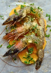 Raw prawns with bread crumbs and parsley on pumpkin slices