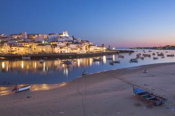 Portugal, Algarve, Ferragudo, Illuminated town and boats in harbor