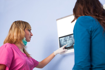 Dentist Examining a Radiography with a Patient