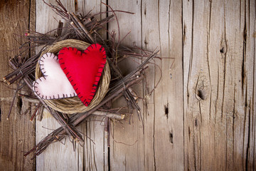 Two felt hearts in a wooden nest