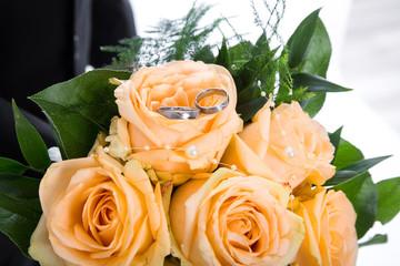 Brautstrauß mit orangen Rosen und Eheringe