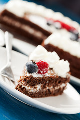 Homemade chocolate cake with cream and berries