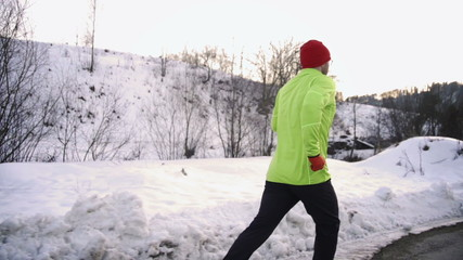Man jogging on the road at wintry day, steady, slow motion