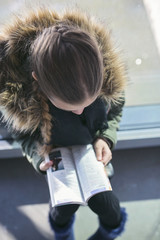 Teen girl (14-15) reading tourist guide book