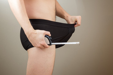 Man pulling his boxers and holding a tape measure