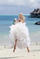 beautiful woman  jumping on edge of sea on beach. Polynesia.