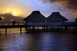 Island in ocean, overwater villas at the time sunset.
