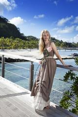 beautiful woman in a long dress on wooden bridge near sea.