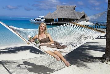 woman in a long sundress in a hammock on a sea background